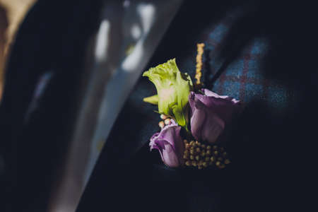 Grooms boutonniere on a jacket of dark blue color. The wedding boutonniere consists of a pink rose, a small dianthus and a chrysanthemum. A man in a white shirt without a tie in a jacket.