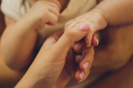 parental hand holds a palm of the baby.
