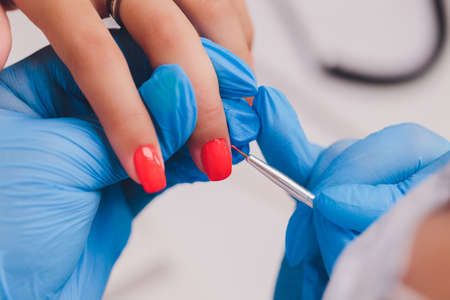 woman doing manicure in a beauty salon. Close-up of hands.