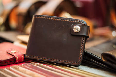 One closed light brown leather mens wallet on a wooden table. View from above.