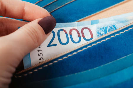 Close-up of a womans hands putting banknote of thousands rubles in a purse. Stock fotó