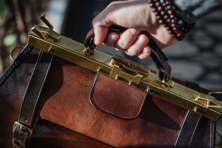 Business man holding elegant brown leather briefcase.