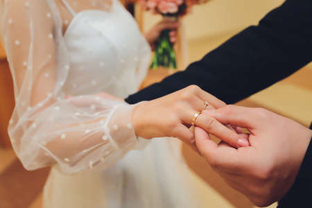 Newlyweds exchange rings, groom puts the ring on the brides hand in marriage registry office. Фото со стока