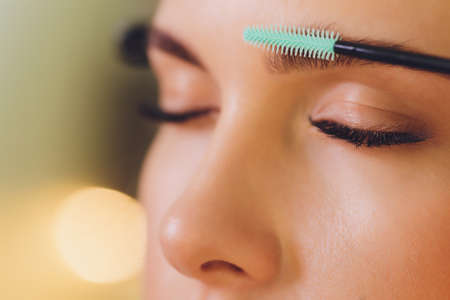 Young woman having professional eyebrow correction procedure in beauty salon.
