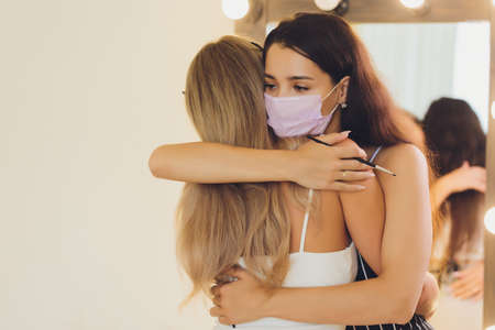 New normal. Two women together with medical protective facial facemask. Girls is hugging at the street. Coronavirus and quarantine concept outdoors. Violation of social distancing.