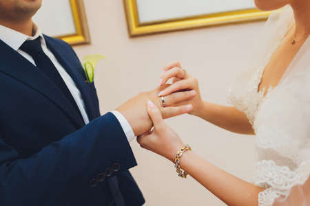 Newlyweds exchange rings, groom puts the ring on the brides hand in marriage registry office. Imagens