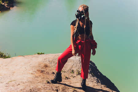 Woman dressed in a steampunk suit in a defiant attitude with her arms crossed. respirator on the face, against the background of a dirty lake