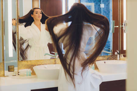 Beautiful woman in the bathroom with long hair. Imagens