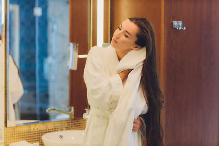 A young woman is standing in a bathroom and drying her hair with a towel. She is looking at the mirror. Horizontally framed shot.