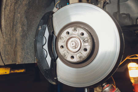 Brake disk and caliper assembly on a modern car about to be replaced. Фото со стока