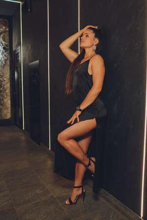 Fashion young women posing in beautiful dress on wall background.