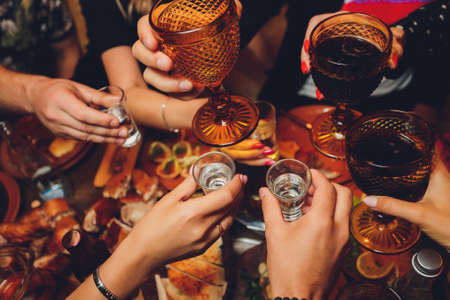 Close up shot of group of people clinking glasses with wine or champagne in front of bokeh background. older people hands. Stockfoto