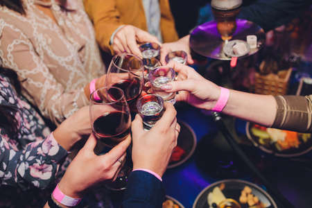 Close up shot of group of people clinking glasses with wine or champagne in front of bokeh background. older people hands.