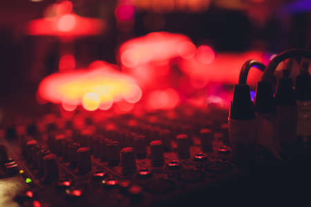 Audio and video jack cable connected at rear end of receiver, amplifier or music mixer at concert, party or festival. Soft effect on photo.