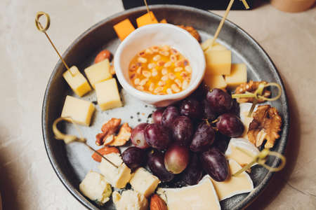 Cheese plate: Emmental, Camembert, Parmesan, blue cheese closeup, with bread sticks and grapes on wooden table. Reklamní fotografie
