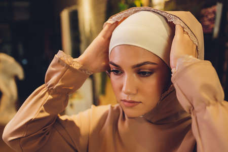 Portrait of positive pretty young Arabian woman in pink headscarf touching face with hand.