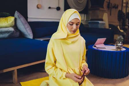 Muslim woman in hijab praying on mat indoors.