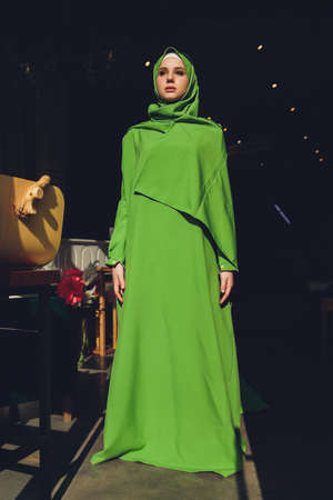 Muslim woman in hijab praying on mat indoors. Stock Photo