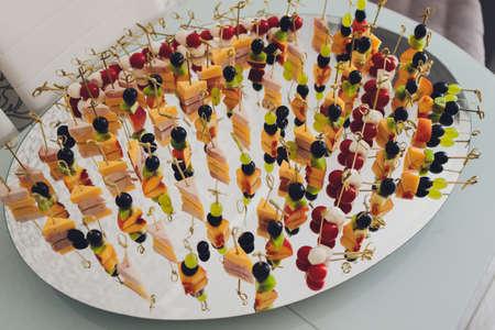 Canape, appetizers, on the table, buffet menu, European cuisine, shrimp, mini burger on a wooden background. 免版税图像