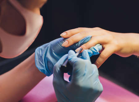 Close-up of beautician applying colorful varnish. Applying nail polish on nails with a brush for applying nail polish on fingers. Manicure nail applicator in a beauty salon. In a beauty salon varnish.