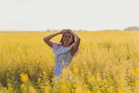 Beauty Girl Outdoors enjoying nature. Beautiful Teenage Model girl in dress running on the Spring Field, Sun Light.