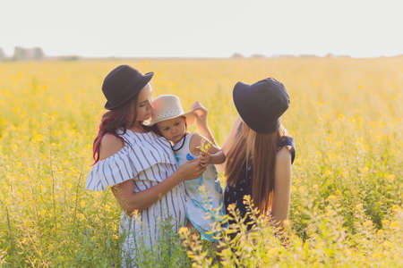 Mothers looking at her daughter and adoring her. Lesbian couple are really happy to adopt a child. LGBT family. Stock fotó