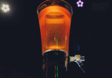 Dispenser and glasses with cold beer on table. Archivio Fotografico