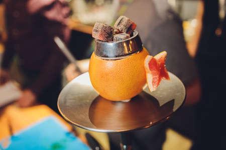 Bowl for shisha from grapefruit with burning coals in white smoke. Zdjęcie Seryjne