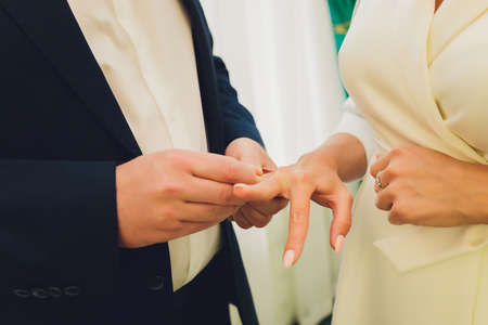 Newlyweds exchange rings, groom puts the ring on the brides hand in marriage registry office. Foto de archivo
