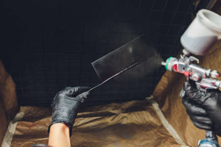 A spray gun in the master s hands is aimed at a test plate and sprays paint in a tinting hood.