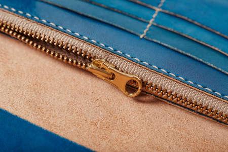 Close up gold zip wallet blue skin.