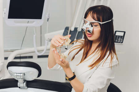 feMale dentist in special glasses with magnifying glasses and mask. Medical worker.