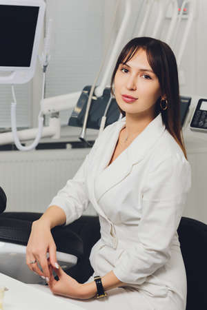 Portrait of attractive smiling female dentist with hands folded. Stock fotó