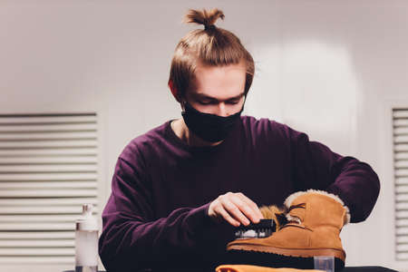 Hands cleaning mens camel suede desert shoe boot with a brush. Footwear maintenance captured from above top view.