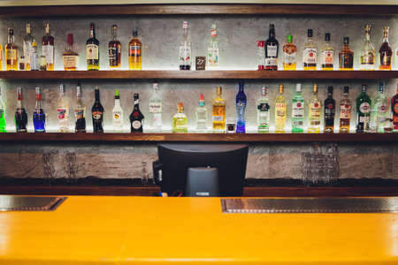 Ufa, Russia, 1 January, 2020: Several types of bottled alcohol are displayed on some shelves in a pub.