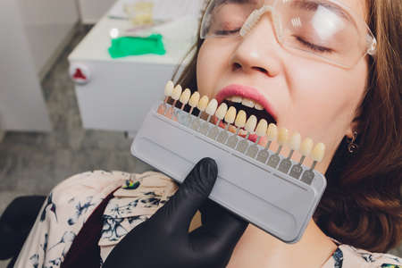 Close up portrait of Young women in dentist chair, Check and select the color of the teeth. Dentist makes the process of treatment in dental clinic office.Dentist.