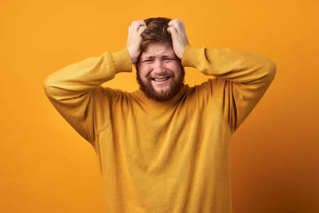 Image of a man in basic clothing, Close up of unhappy handsome guy with beard holding hair with hands. isolated on a yellow background. The bearded man