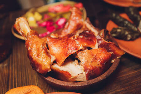 Pork knuckle on wooden surface. Horisontal pork knuckle on round wooden table with side dish, close-up. Standard-Bild - 158700168