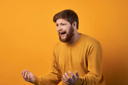 Portrait of emotive annoyed irritated unshaven male clenches teeth and gestures angrily while argues with wife, has irritated negative facial expression, wears casual white t shirt, stands indoor. Standard-Bild