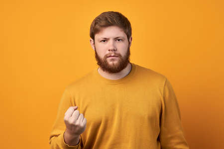 Angry strict man with thick beard, being furious, expresses warning and threat, shows his power or resoluteness, wears casual t shirt, isolated on pink background, looks with serious expression. Standard-Bild