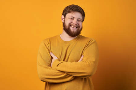 Attractive swedish man with stylish hair and beard laughs at funny story from friend with crossed hands and closed eyes. Standard-Bild