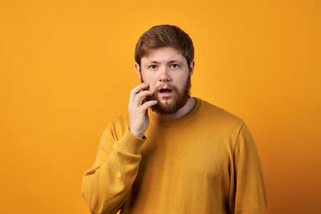 Astonished attractive male has ginger long beard, wonders sudden news, keeps mouth slightly opened, stares at camera, wears casual clothes and spectacles, poses against white wall with blank space. 版權商用圖片