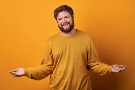 Beautiful bearded man with stylish hairdo smiling and spreading hands dont know what to say in answer. Body language. Standard-Bild