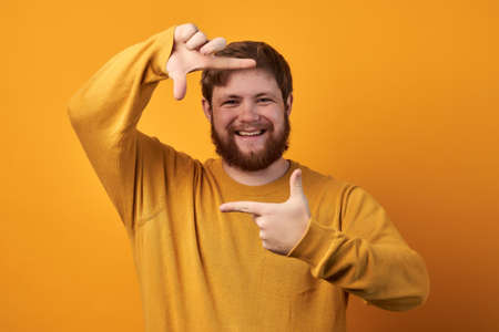 Cheerful satisfied unshaven man makes frame sign with both hands, prepares for being photographed, dressed in casual red t shirt, stands against white background. Look at life from bright angle. Standard-Bild
