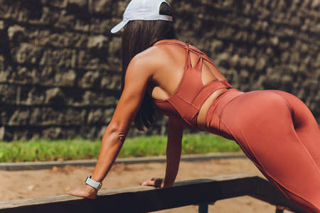 A beautiful young woman is engaged in sports on a street simulator. Concept of good physical shape and healthy lifestyle. Standard-Bild - 158724482