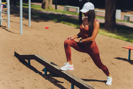A beautiful young woman is engaged in sports on a street simulator. Concept of good physical shape and healthy lifestyle. Standard-Bild - 158723940