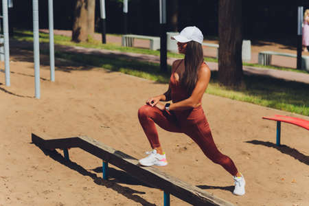 A beautiful young woman is engaged in sports on a street simulator. Concept of good physical shape and healthy lifestyle. Standard-Bild - 158724050