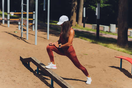 A beautiful young woman is engaged in sports on a street simulator. Concept of good physical shape and healthy lifestyle. 免版税图像