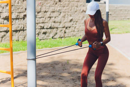 A young sportswoman with elastic band doing exercise outdoors in city.