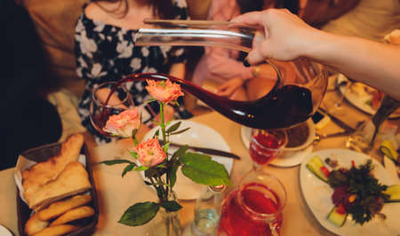 Sommelier pouring wine into glass from mixing bowl at luxury diner. Standard-Bild